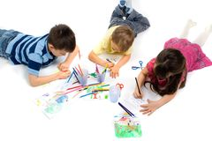 Three Children Drawing on Floor Royalty Free Stock Images
