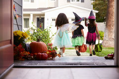 Three Children In Halloween Costumes Trick Or Treating Stock Images