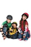 Three Children in Helmets. Three young children wearing protective skate gear.  Two boys and one girl sit together smiling.  Helmets and padding are visible Stock Images