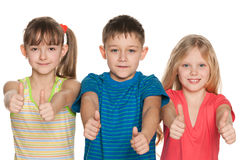 Three children hold their thumbs up Royalty Free Stock Photography