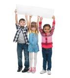 Three children  holding empty sheet of paper Stock Image