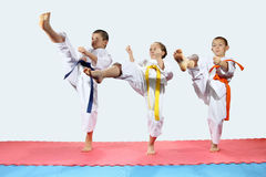 Three children in karategi are beating kick leg forward Royalty Free Stock Images