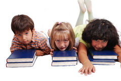 Three children laying down on books isolated Royalty Free Stock Photography