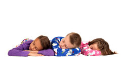 Three children laying down in their warm winter pajamas Stock Image