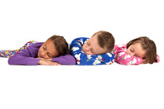 Three children laying down in their warm winter pajamas Royalty Free Stock Image