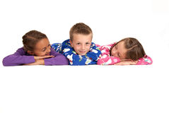 Three children laying down in their winter pajamas Stock Photo