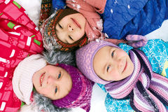 Three children lie on the snow in winter and looking upwards Stock Photos