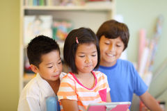 Three children look at a tablet computer Royalty Free Stock Image