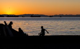 Three children looking out across the water towards the sunset. royalty free stock images
