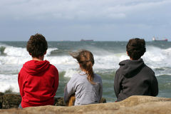 Three children looking out to sea royalty free stock images