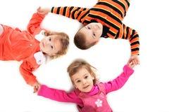 Three children lying Stock Images