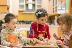 Three children make dough cookies. Three children make dough cookies royalty free stock photo