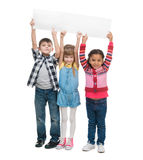 Three children with open mouths holding empty sheet of paper Royalty Free Stock Image