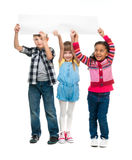 Three children with open mouths holding empty sheet of paper. Isolated on white background Stock Photography