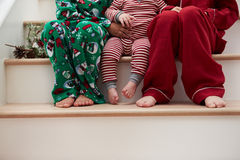 Three Children In Pajamas Sitting On Stairs At Christmas Stock Image