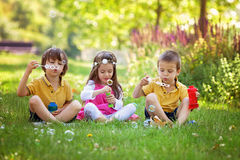 Three children in the park blowing soap bubbles and having fun Stock Images