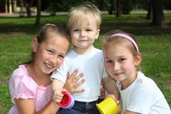 Three children in park in summer Stock Photos