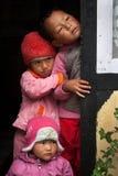 Three children peeping Stock Photos