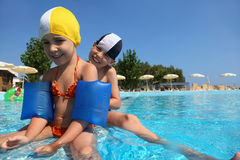 Three children play in day-time in pool Stock Photo