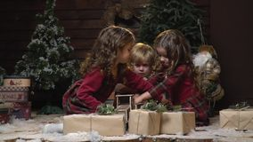 Two girls in dresses play with a fair-haired little boy sitting among the dodark and Christmas trees in a cozy room. Three children play with toys in the room stock footage