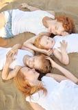 Three children playing on beach Stock Photos