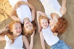 Three children playing on beach Stock Photo
