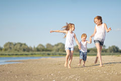Three children playing on beach Stock Images