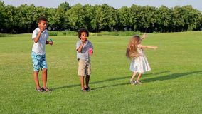 Three children are playing on the evening glade. stock footage