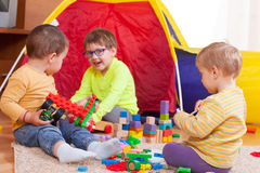 Three children playing on  floor. Two girls and boy with toys on  floor at home Stock Photography