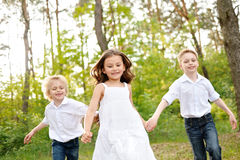 Three children playing on meadow Stock Photo