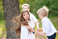 Three children playing on meadow Stock Photos