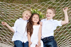 Three children playing on meadow Stock Images