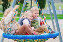Three children playing in the park. With swing royalty free stock image