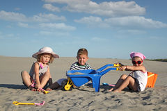 Three children playing in sand Royalty Free Stock Images