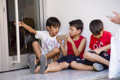 Three Children Are Playing With Smartphones Royalty Free Stock Images