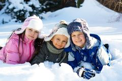 Three Children Playing in Snow. Three happy, smiling children take a few moments to pose while playing outside in the snow on a cold winter day Royalty Free Stock Photos