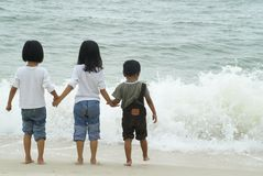 Three children playing with waves. Three ethnic asian children standing together while attempting to step into crashing waves at the beach Stock Images