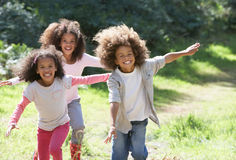 Three Children Playing In Woods Together Stock Images