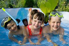 Three Children In Pool. Three children, two boys with a girl in the middle, lined up in a wading pool.  Both boys are wearing goggles and flippers.  One boy has Stock Image