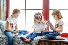 Three children read, draw and write. A group of children is stud. Ying. The concept is childhood, learning, drawing, hobbies, education stock images