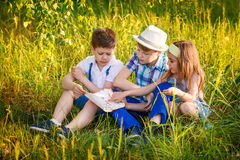 Three children read together in the summer. Brother and sister portrait in the village stock image