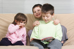 Three children reading book. Sitting on brown sofa Royalty Free Stock Image