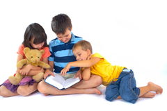 Three children reading book. Three caucasian children reading a book on white studio background.The girl is holding a teddy bear while the boy in the center is Stock Image