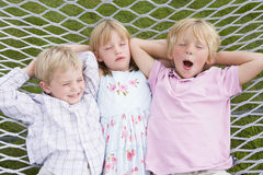 Three children relaxing and sleeping in hammock. High angle view of three children relaxing and sleeping in hammock Royalty Free Stock Image