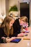 Three children at a restaurant using iPads stock photography