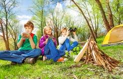 Three children resting near the wooden bonfire Stock Photos