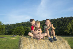 Three children on the roll of hay in the meadow Royalty Free Stock Photography