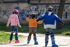 Three Children Roller Blading Royalty Free Stock Photography