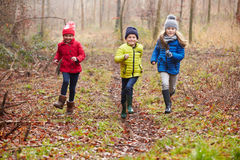 Three Children Running Through Winter Woodland. Three Happy Children Running Through Winter Woodland Towards Camera stock photos