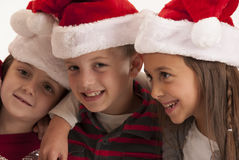 Three children in santa hats smiling Royalty Free Stock Photography